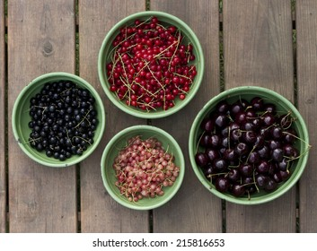 Fresh fruit in a rustic bowl. cherry carrant bleu berry white currant on a wooden background