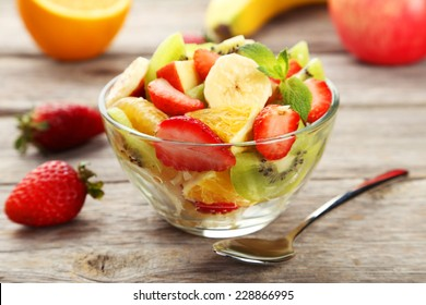 Fresh fruit salad in bowl on grey wooden background