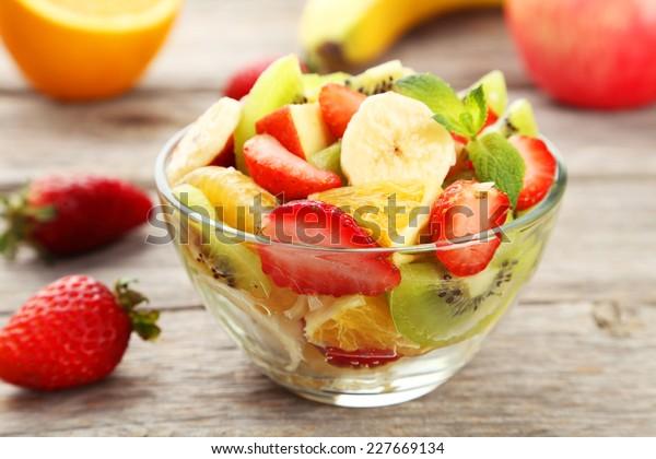 Fresh fruit salad in bowl on grey wooden background