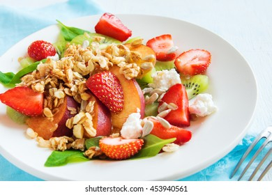 Fresh fruit salad with granola, feta cheese and honey on white plate for healthy breakfast