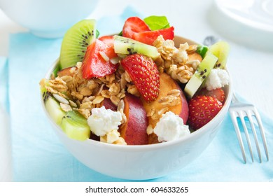 Fresh fruit salad with homemade granola, feta cheese and honey on white plate for healthy vegan diet vegetarian organic breakfast, food, meal, salad