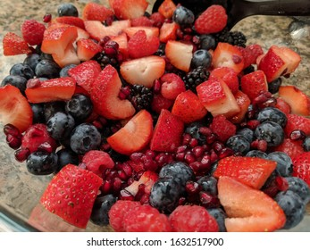 A fresh fruit salad of strawberries, raspberries, blackberries, blueberries and pomegranate seeds