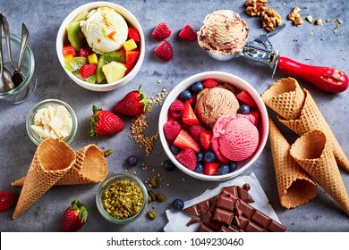 Fresh fruit with scoops of creamy speciality ice cream in assorted flavors with raspberry, berry, blueberry, strawberry, walnut , pistachio, chocolate, sugar cones and a scoop for serving from above
