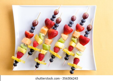Fresh fruit shish kebabs arranged diagonally on a modern square plate for a healthy vegetarian buffet or dessert, viewed from above on a yellow summer table