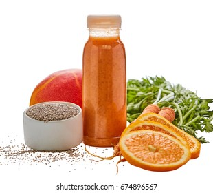 Fresh fruit and vegetable smoothie still life on white with orange, carrots, mango and chia seeds around a bottle of blended ingredients