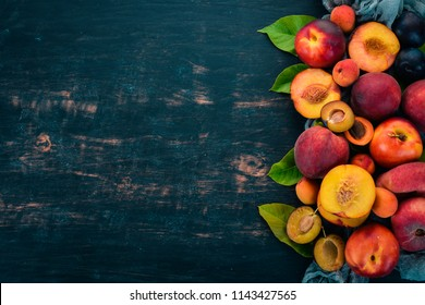 Fresh fruits. Apricot, peach, plums, nectarines. On a wooden background. Top view. Free space for text.