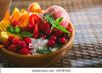 Fresh fruits apricots, raspberries and strawberries on ice.
