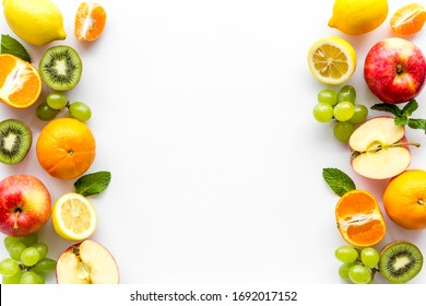 Fresh fruits background with citruses, apple, kiwi and grape on white table top-down frame copy space