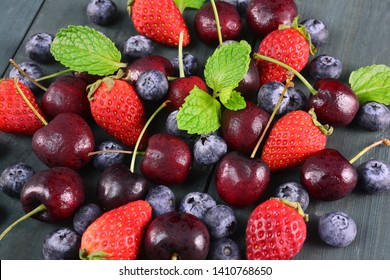 Fresh fruits berries, strawberry, cherries, blueberry on wooden background.