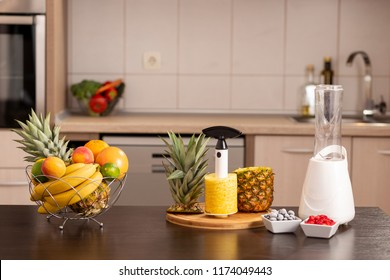 Fresh fruits in a bowl and a pineapple peeled with pineapple cutter on a kitchen counter next to a smoothie maker