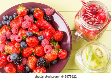Fresh fruits flavored water healthy detox drinks in jars and plate of soft fruits - top view