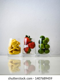 Fresh fruits in glass with white background and reflection. From right to left: sliced bananas, strawberries, and calamansi lemons.