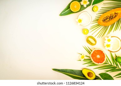 fresh fruits with green tropical leves flat lay border, summer diet background, toned