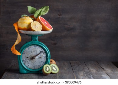 Fresh fruits on the old vintage kitchen scale on the wooden background