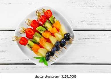 Fresh fruits on skewers in plate on wooden table, top view