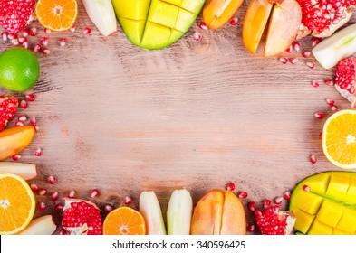 Fresh fruits on a wooden background. Raw and vegetarian eating frame. Sliced orange, persimmon, kiwi, tangerine, banana, lemon, apple,  grapefruit, pomegranate, lime, mango. Top view. Fruit set.