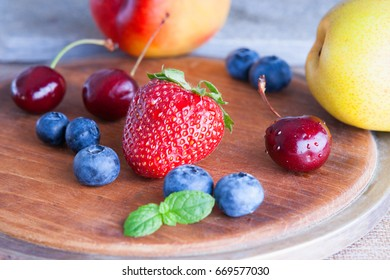 Fresh fruits on a wooden cutting board