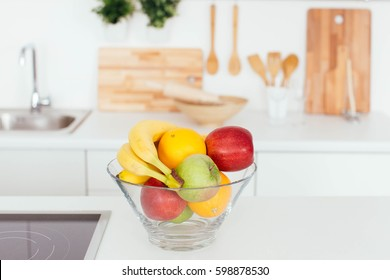 Fresh fruits - orange, banana, aplle - in a glass bowl in a kitchen
