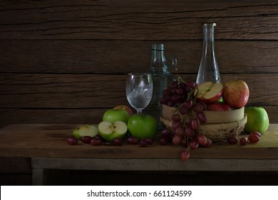 Fresh fruits in the rattan basket and bottle with glass on the plank in room it dim light / Still Life Image and selective focus, Space for text