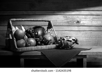 Fresh fruits in the rattan basket on wooden plank and old wooden wall in the room which has dim light / Still Life image and adjustment color black and white style