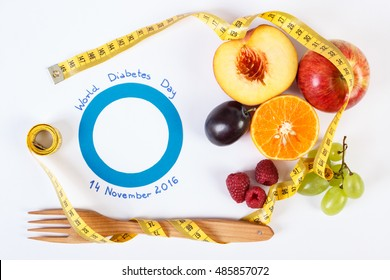 Fresh fruits with tape measure and blue circle of paper, concept of slimming and symbol of world diabetes day. White background