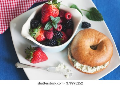 Fresh fruits with toasted whole-wheat bagel and herb cream cheese.