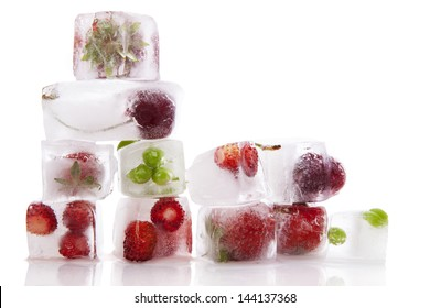 Fresh fruits and vegetable frozen in ice cubes isolated on white background. Fresh healthy summer eating.