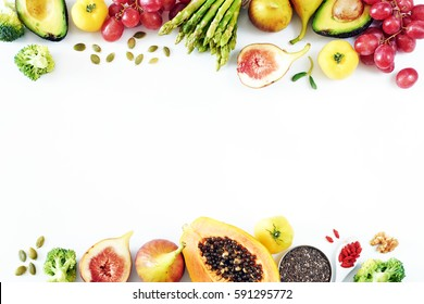 Fresh fruits and vegetables food frame over white background with empty space. Top view of papaya, avocado, tomato, grape, asparagus, figs, broccoli, goji, chia, pumpkin seeds.