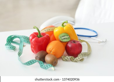 Fresh fruits and vegetables with measuring tapes on table of nutritionist in office
