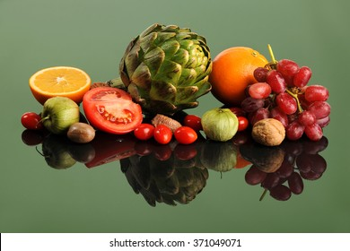 Fresh fruits and vegetables on reflective table with green background