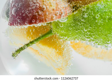 Fresh fruits in water wiht air bubbles. Close-up photo.