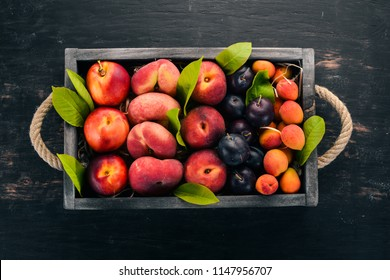 Fresh fruits in a wooden box. Apricot, peach, nectarine, plum. On a wooden background. Top view. Free space for your text.