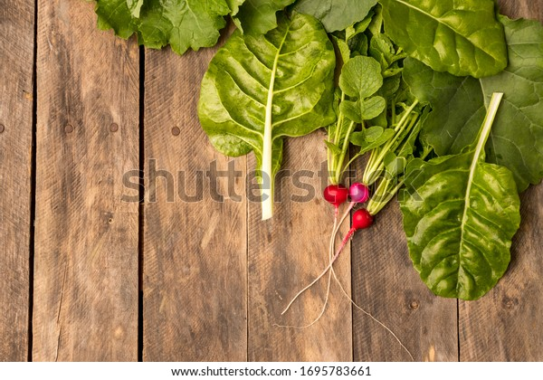 Fresh garden greens on rustic wood table flat lay healthy