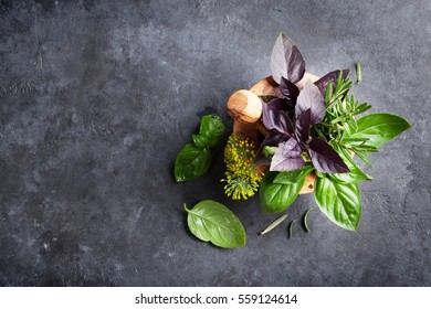 Fresh garden herbs in mortar on stone table. Basil, rosemary, dill. Top view with copy space