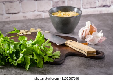 Fresh garden herbs on kitchen countertop. Parsley, garlic, knife and almons. The concept of food, healthy food.