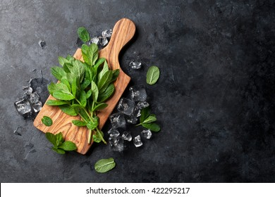 Fresh garden mint and ice on stone table. Top view with copy space