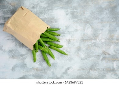 Fresh from the garden organic English peas in brown paper bag on rustic wooden background.  In flat lay composition, horizontal format with room for text