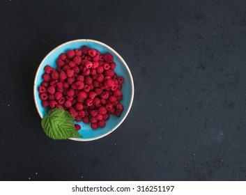 Fresh garden raspberries in blue ceramic bowl over grunge black background, top view, copy space