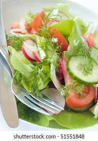 Fresh garden salad with a fork and knife.