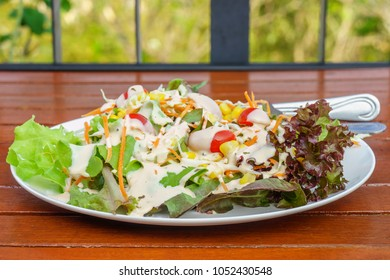 Fresh garden salad with tomatoes, carrots, corn and dressing on a table. A mixture of small pieces of vegetable in a dish.