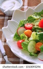 Fresh garden salad in white flower bowl in vertical format and shot in natural light