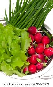 fresh garden vegetables in a colander over white