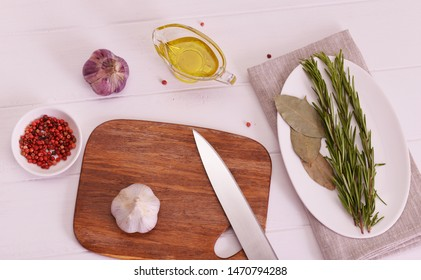 Fresh garlic on a cutting board on a wooden white background with spices around. Raw garlic and spices on wooden table.