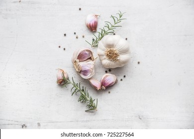 Fresh garlic with rosemary and pepper on white concrete board.