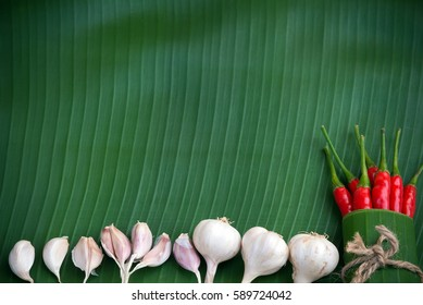 Fresh garlic,red chili pepper on green banana leaf background.