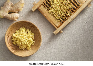 Fresh ginger granules in washboard and wooden plate,  fresh root ginger on the linen