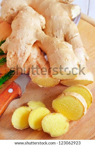 Fresh ginger and knife on the wooden board