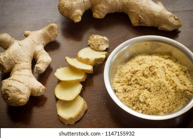 Fresh ginger root and ground ginger on wooden background.