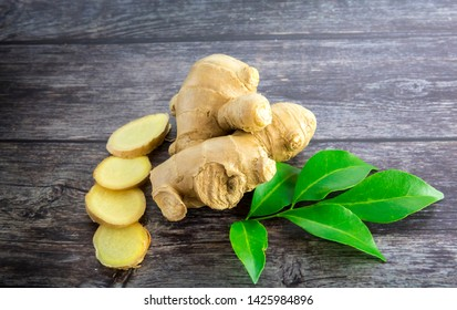 Fresh ginger slices on black wooden background, raw material for food and herb medical concept