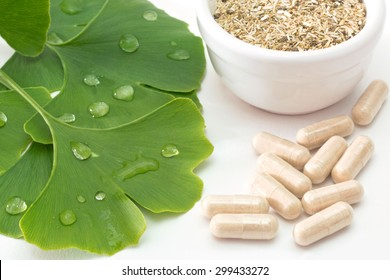 Fresh ginkgo leaves with dried herb and capsules on white background